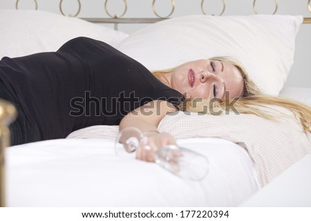 Drunk woman in black shirt with glass, sleeping in bed
