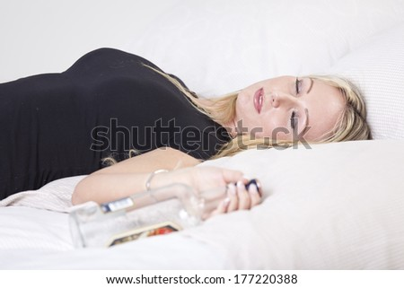 Drunk woman lying on bed, holding a bottle of alcohol
