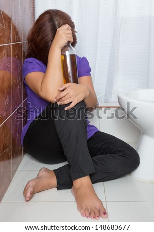 Drunk woman sitting in the bathroom and holding a liquor bottle