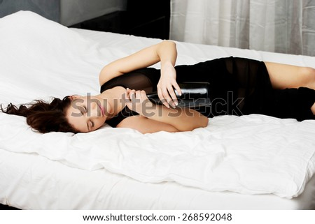 Drunk woman sleeping on bed with bottle of wine. - stock photo