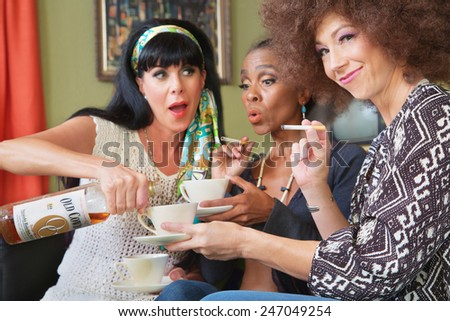 Drunk woman tempting friends with whiskey in teacups - stock photo