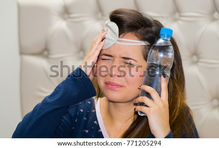Drunk woman with a sleeping eye mask in her head and with a bottle of water pressing in her head using her other hand, hangover concept