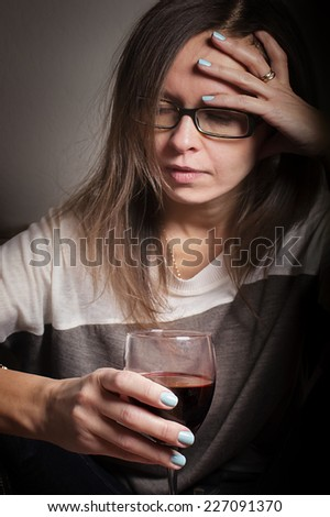 Drunk woman with half empty glass of wine having headache, indoor vertical shot with selective focus on glass - stock photo