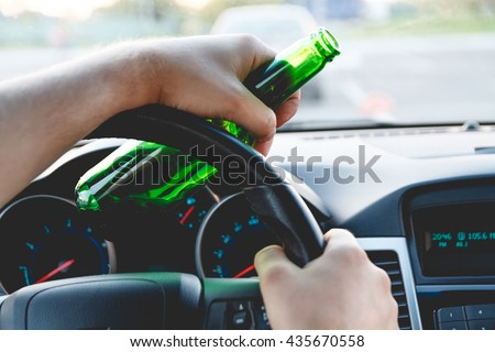 Drunk young man driving a car with a bottle of beer. Don't drink and drive concept. Driving under the influence. DUI, Driving while intoxicated. DWI - stock photo