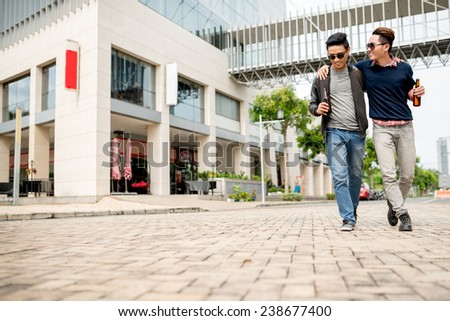 Drunk young people with beer bottles hugging and walking along the street - stock photo
