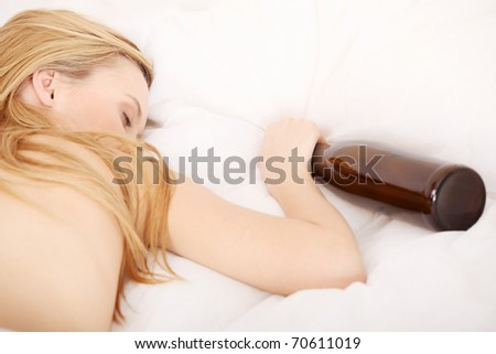 Drunk young topless woman sleeping on bed with bottle of vine in hand. Isolated on white - stock photo