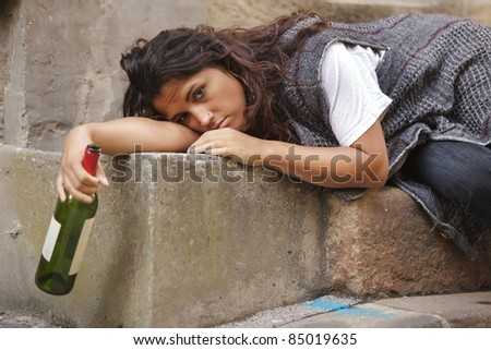 drunk young woman holding bottle of wine lying on stone stairs - stock photo