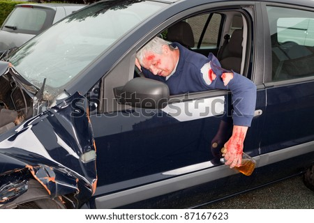 Drunken driver hanging out of his crashed car - stock photo