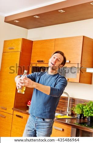 Drunken man holding bottle of whiskey - stock photo
