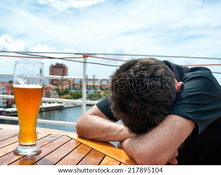 Drunken man with Head Down on Table Next to Glass of Beer Outdoors on Patio - stock photo
