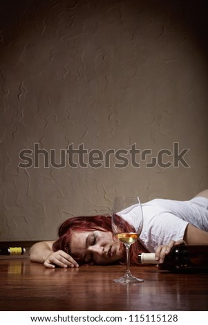 Drunken young woman lying on the floor. Focus on glass