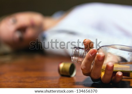 Drunken young woman lying on the floor. Focus on the bottle - stock photo