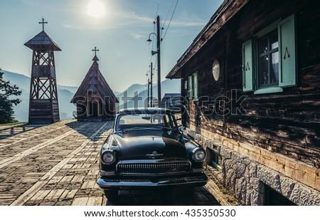 Drvengrad, Serbia - August 28, 2015. Old Volga car in front of wooden house of Drvengrad village built by Emir Kusturica - stock photo