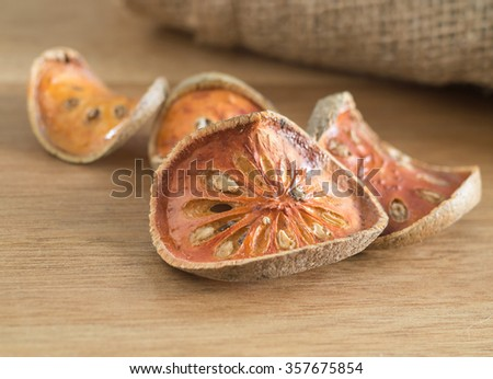 Dry Aegle marmelos ( bael fruit )on wooden table - stock photo