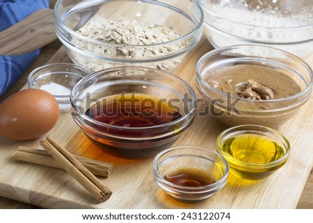 Dry and liquid ingredients for baking including an egg and cinnamon sticks - stock photo