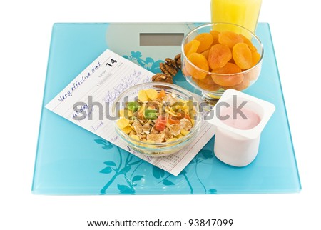 dry apricot, muesli, nuts,  yogurt, juice  and note of diet are situated on scales filmed closeup - stock photo