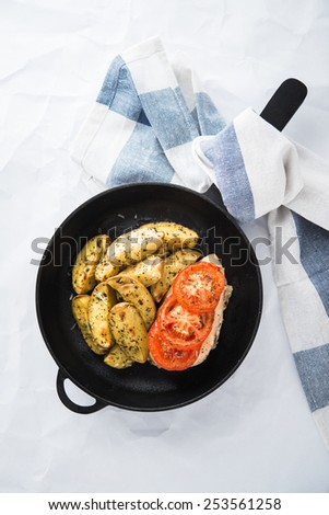 Dry basil parmesan fries and tomato chicken oven baked in cast-iron pan top view on white background. - stock photo