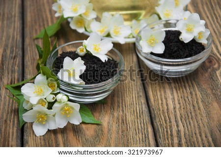 Dry black jasmine tea with jasmine flowers in bowls on a wooden background