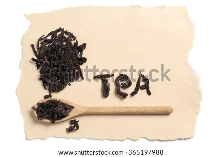 Dry black tea in spoon and paper on white background. Word tea. Top view - stock photo