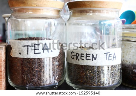 Dry black tea leaves in bottles - stock photo