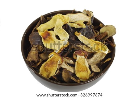 dry boletus in brown dish on white background - stock photo