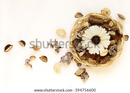 dry brown flowers, leaves, petals in wicker basket on white background - stock photo