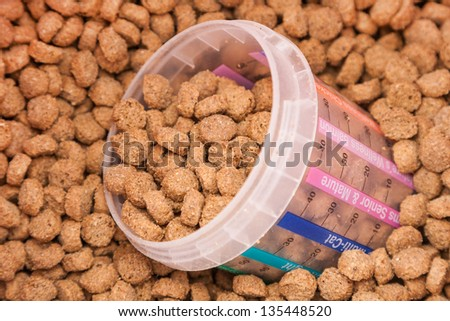 dry brown grained pets food with measured glass - stock photo