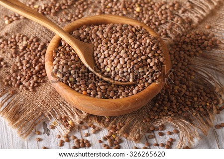 Dry brown lentils in a wooden bowl on the table close-up. Horizontal, rustic - stock photo