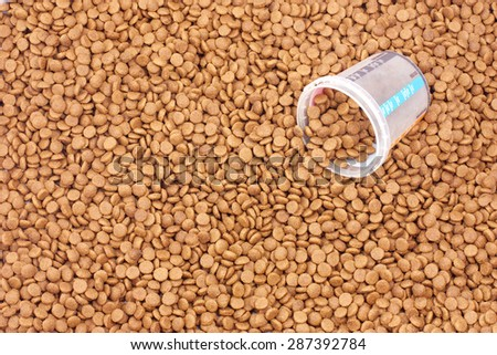 Dry brown pet food (dog or cat) with measure glass - stock photo