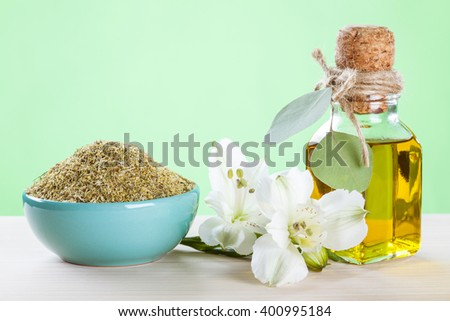Dry camomile in a bowl and a bottle of organic oil on wooden table - beautiful skincare composition