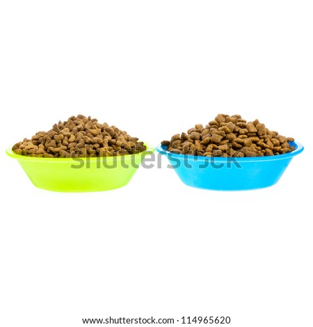 Dry cat food in plastic bowls isolated on white background - stock photo