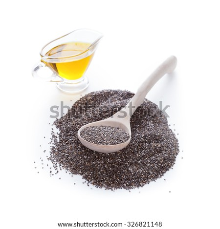 Dry chia seeds in spoon on Omega3 plant oil background - stock photo