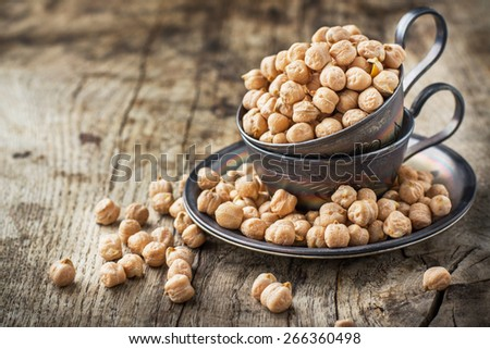 Dry chickpeas in a vintage German silver cup on dark wooden background. selective Focus - stock photo