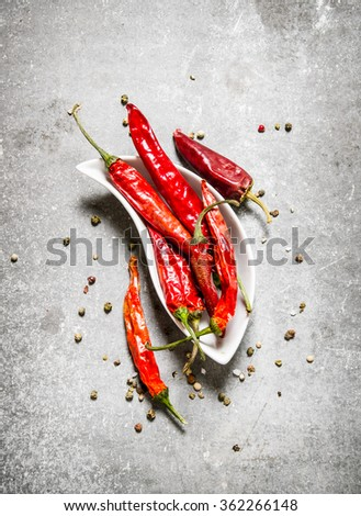 Dry chili pepper in a Cup. On a stone background. Top view - stock photo