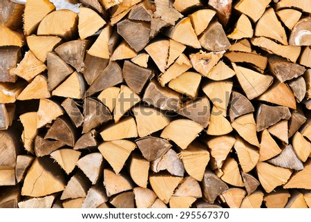Dry chopped firewood logs in a pile - wood background - stock photo