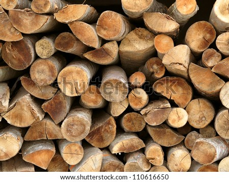 Dry chopped firewood logs stacked up on top of each other in a pile - stock photo