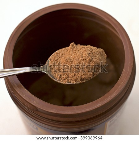 Dry cocoa powder on a spoon with sugar - stock photo