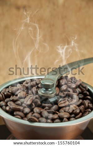 Dry coffee beans with smoke in coffee grinder - stock photo