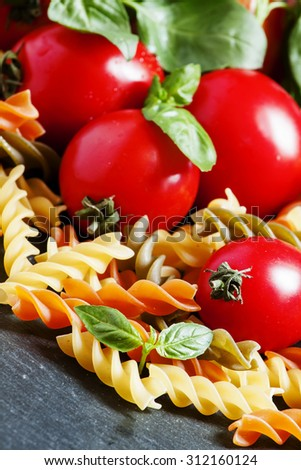 Dry colored fusilli pasta, tomatoes and basil, selective focus