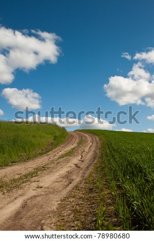 dry cracked dirt road in the middle of a field heading to the sky
