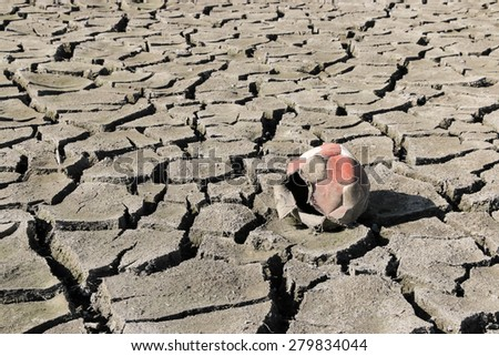 Dry cracked earth and old torn soccer ball - stock photo