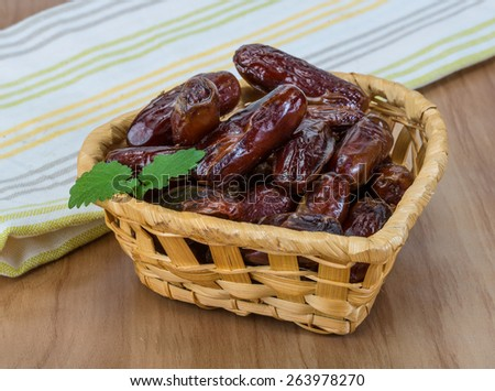 Dry Dates fruit in the bowl on the wood background - stock photo