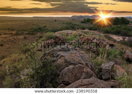 dry desert farmland with sunlight on the distant horizon with rocks and scrub in the foreground - stock photo