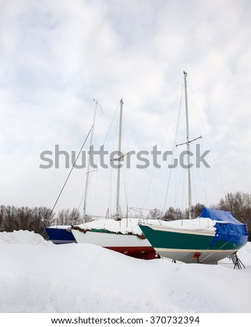 Dry Docked Sailboats - Three sailboats side by side in the snow.  Stored on land for winter.  Waiting for Spring. Copy space. - stock photo