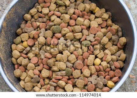Dry dog food contained in a metal bowl. Closeup image of different coloured dry dog food. - stock photo