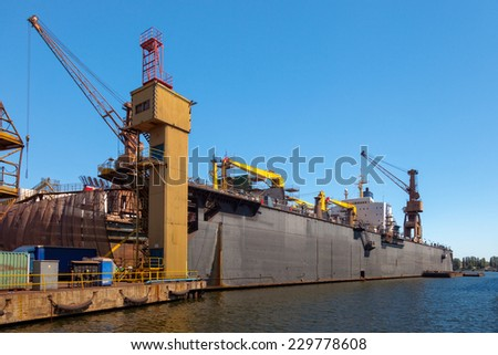 Dry floating dock and cranes in shipyard.  - stock photo