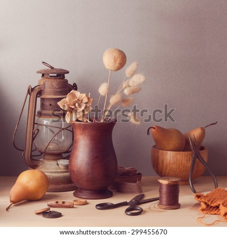 Dry flowers and pears on wooden table. Rustic still life - stock photo