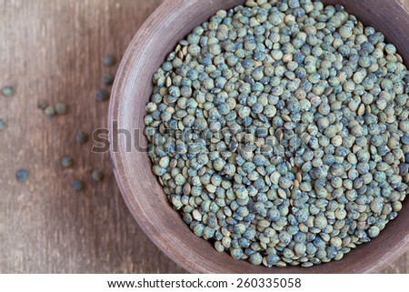 Dry green french lentils (Du Puy) in a clay bowl on wooden table, selective focus - some beans in focus, some are not - stock photo