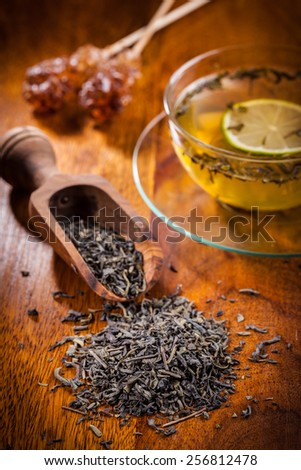 Dry green tea on wooden table - stock photo