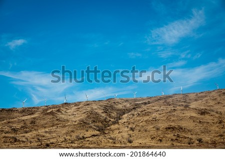Dry hill on Maui with wind turbines - stock photo
